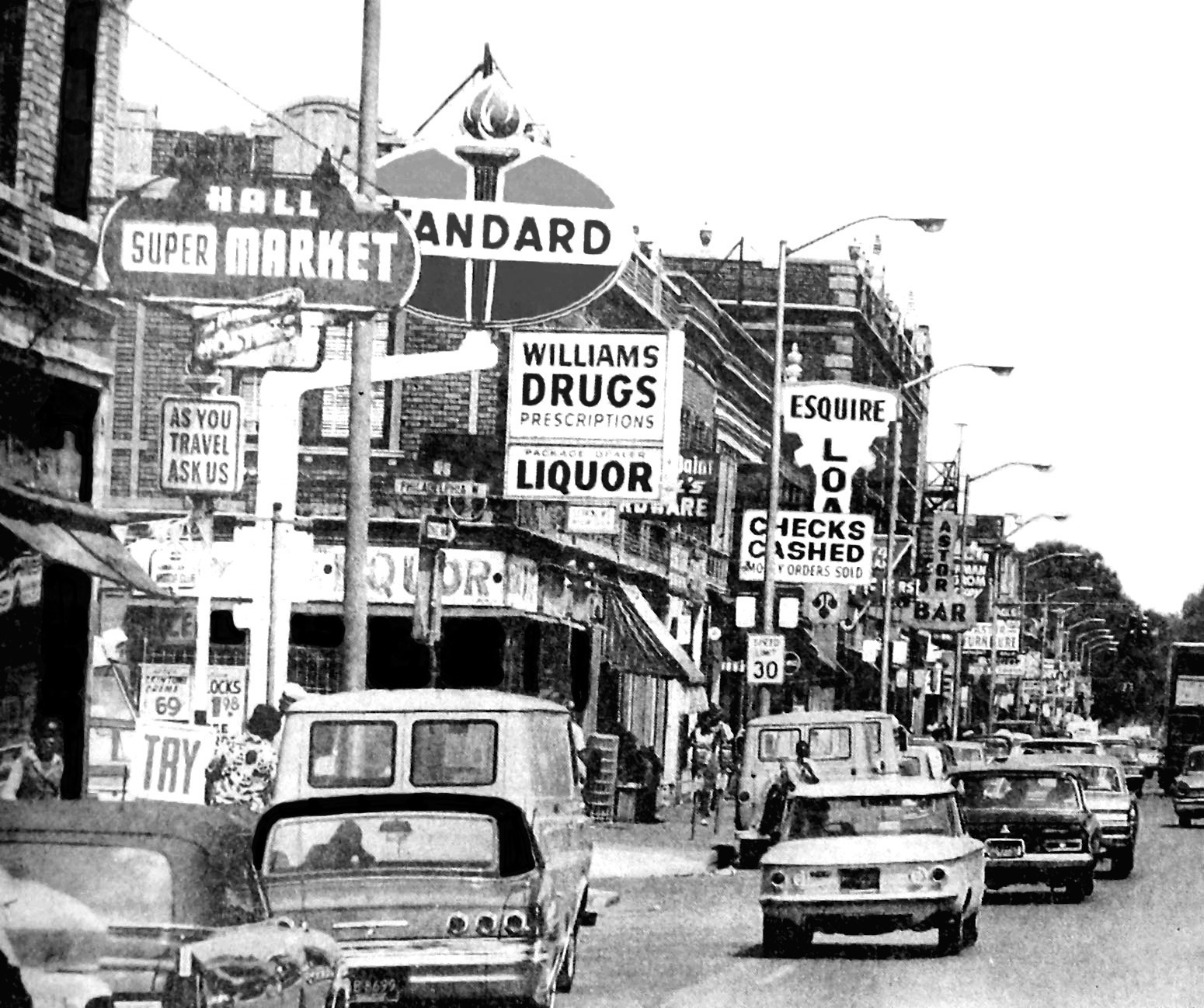 Black and white photograph of Black Bottom street scene from the 1940s with cars and street signs.