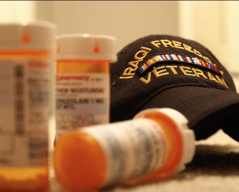 Iraq veteran baseball hat with prescription medicine bottles stock image from Wikimedia Commons