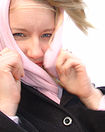 Photo of woman from shoulders up with wind blowing holding a pink scarf over her head and covering her cheeks and mouth. She is wearing a black wool coat.