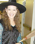 Photo of teacher wearing a witch's hat, black shirt, and holding a thin broom.