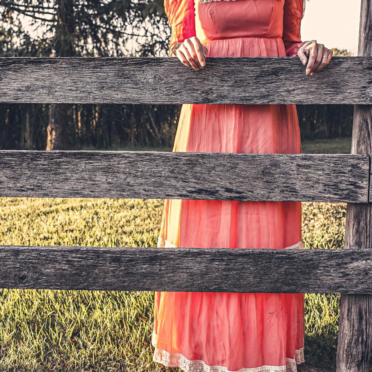Color photo of a thin woman from her midsection to her feet, wearing a full length peach dress with yellow on the sides, standing behind three horizontal beams of an aged wooden fence spaced about a foot apart. Stock photo courtesy of Gratisography.com