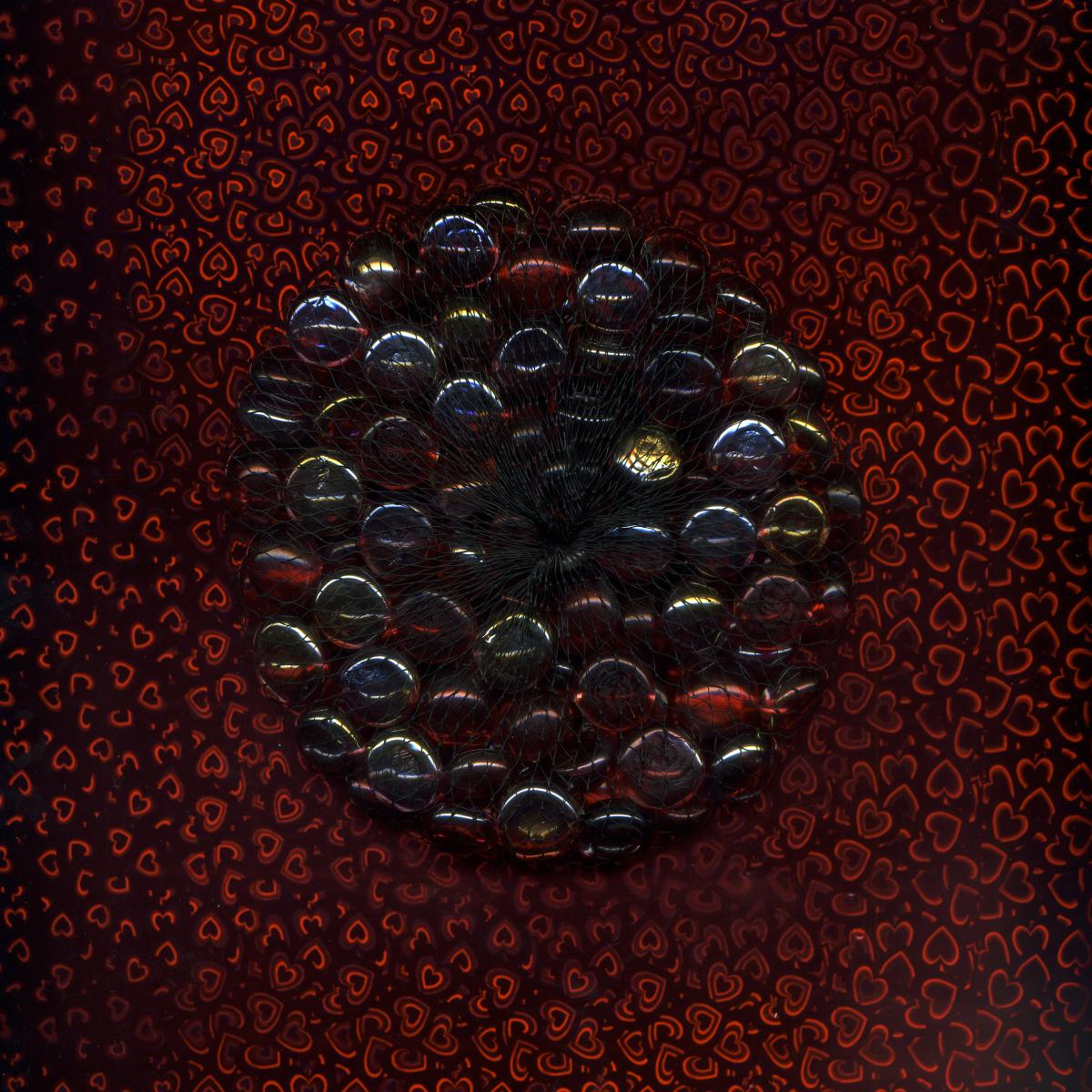 Photograph of dark glass beads forming a sphere on a dark red textured background.