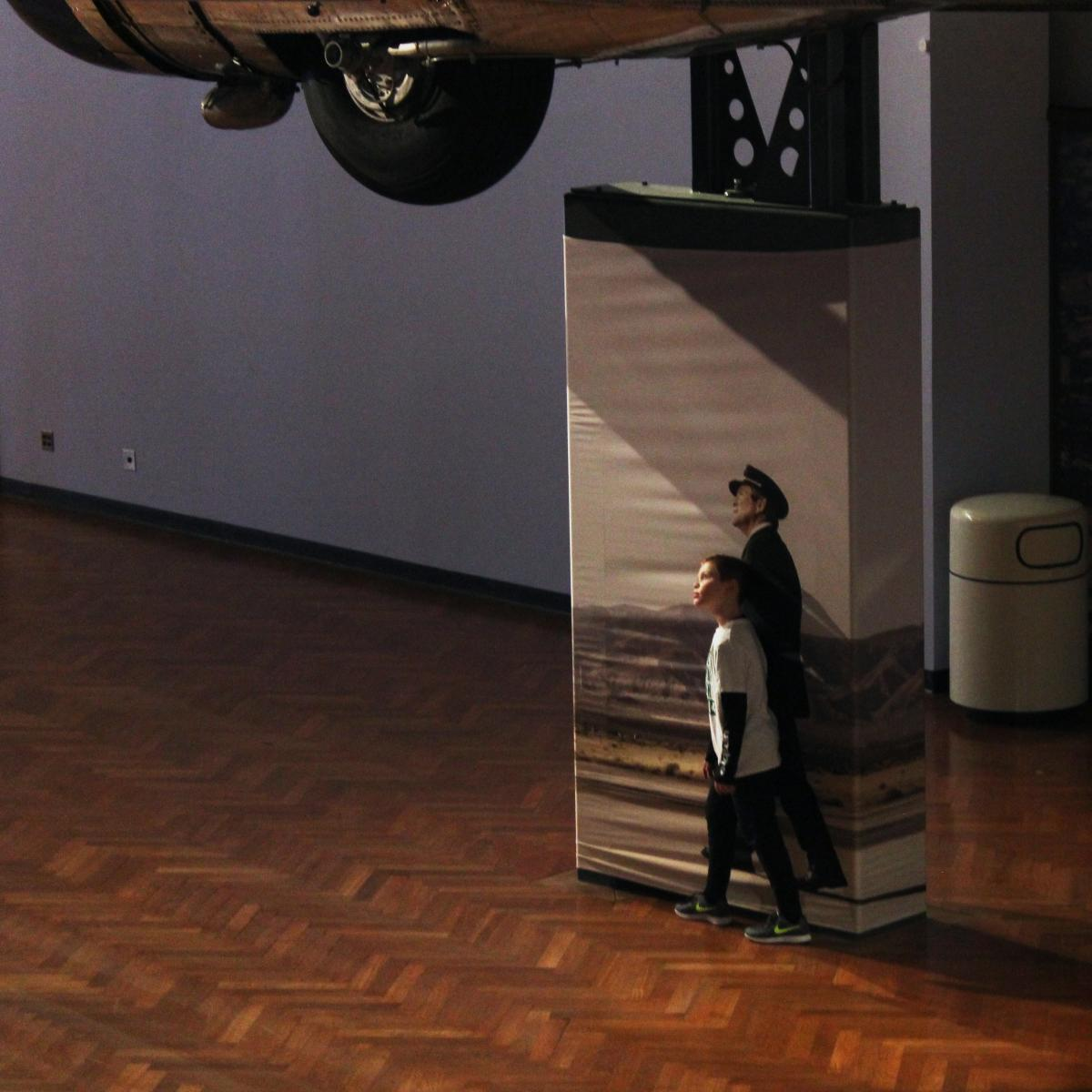 Photo of boy standing next to the image of a pilot as if he is part of the image underneath an airplane hanging at The Henry Ford museum in Dearborn, Michigan.