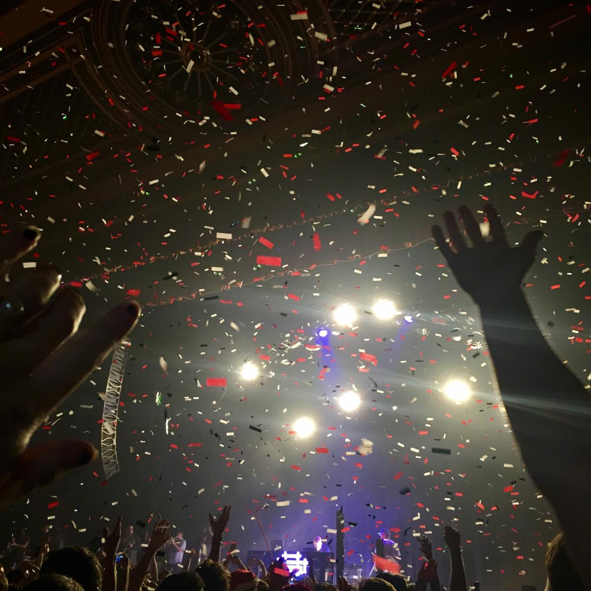 Concert photo with crowd and hands in the air and bright stage lights.