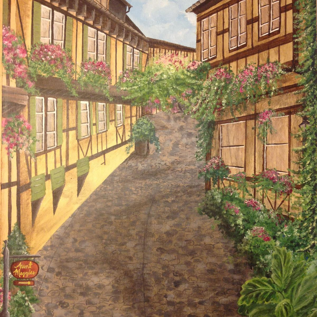Oil painting of cobblestone street with two story village buildings with ivy covering them; appears like a European village in the summer.