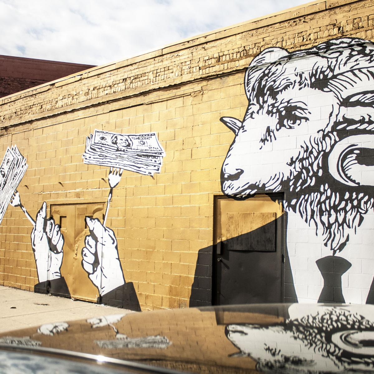 Mural of two goat people wearing black and white suit and tie holding forks spearing stack of dollar bills.