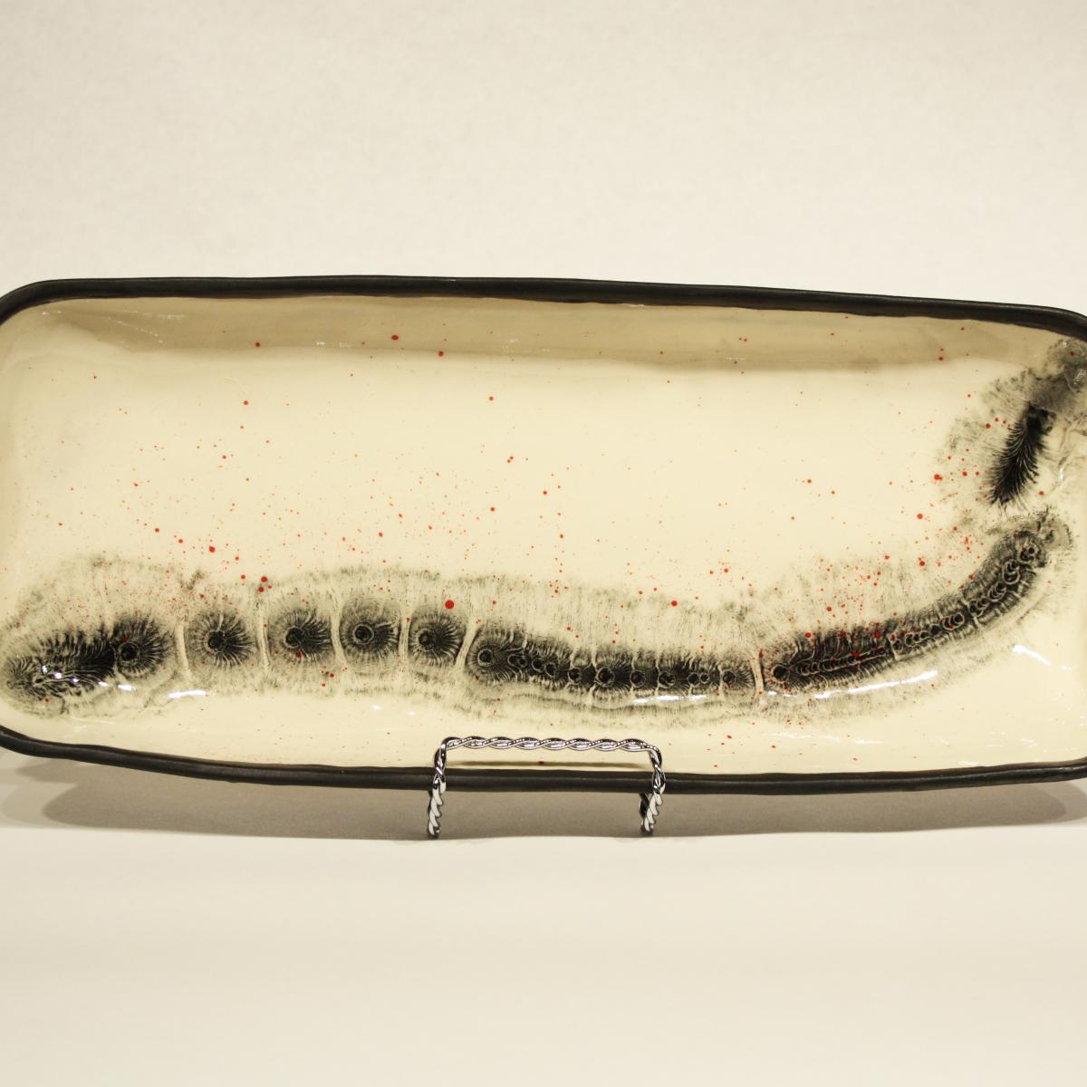 Long rectangular serving platter with handles with black snakelike pattern on white.
