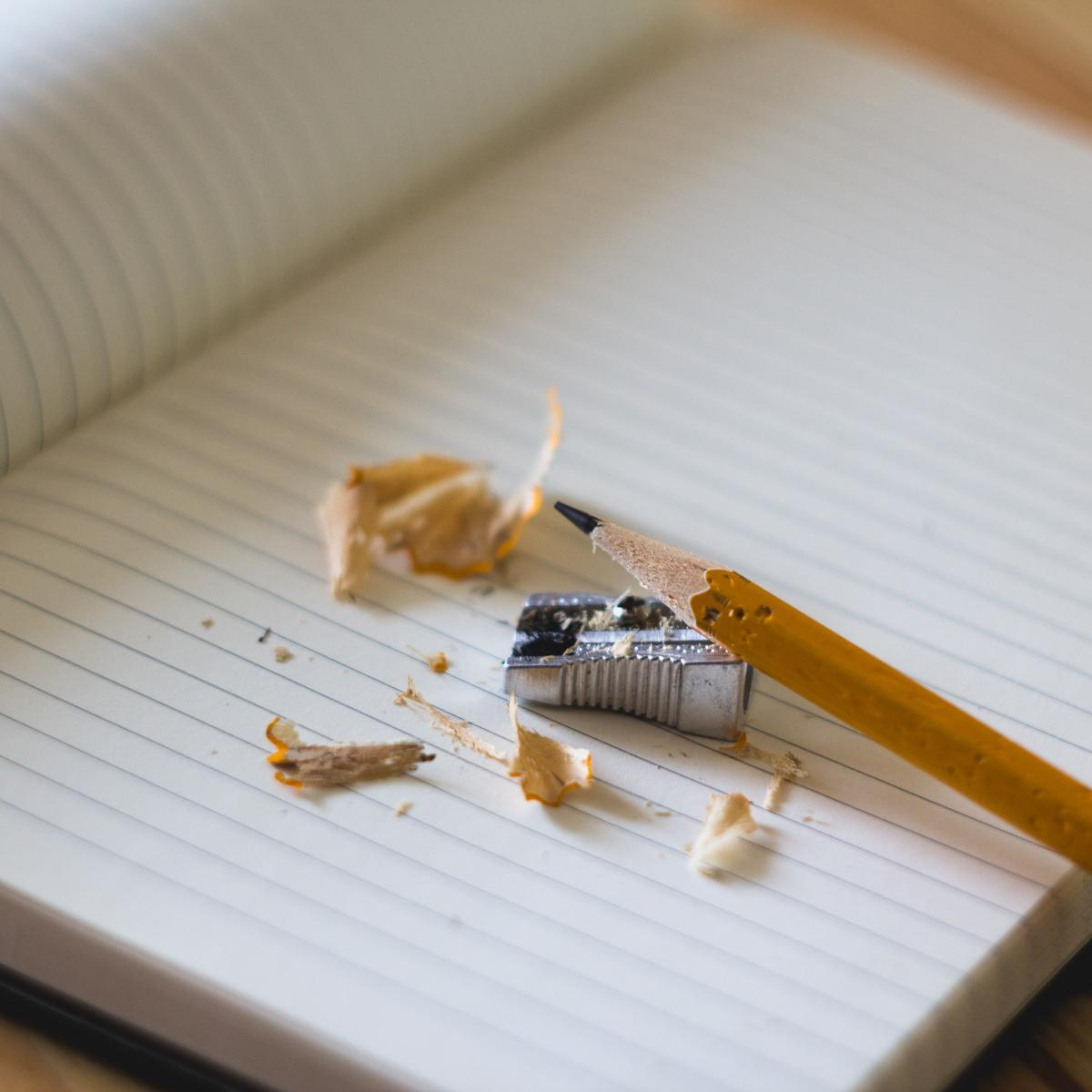 Photo of open notebook with blank lined pages sitting on a desk. On the page is a pencil and pencil shavings. Photo by Angelina Litvin from StockSnap.io