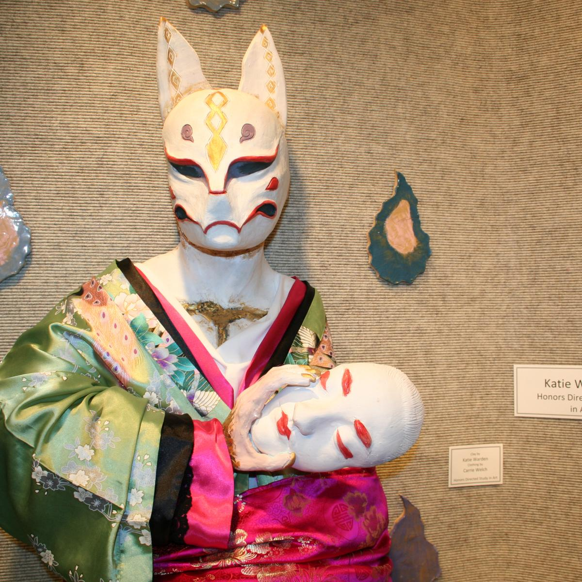 Ceramic cat mask with female body in kimono holding human mask