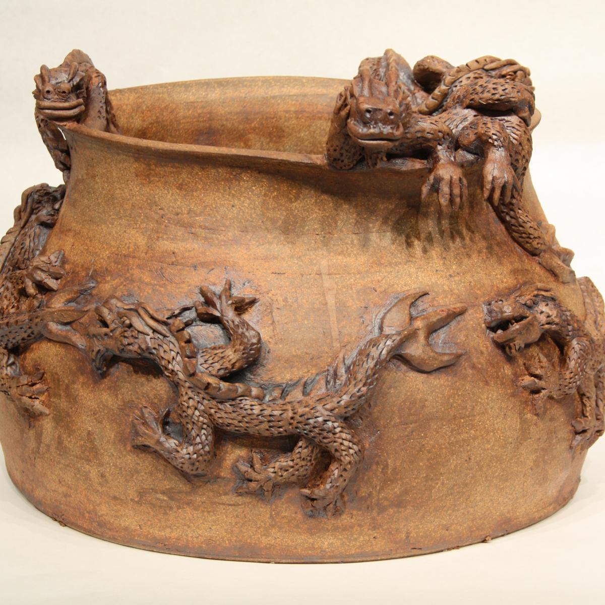 Brown pottery with dragons around it.