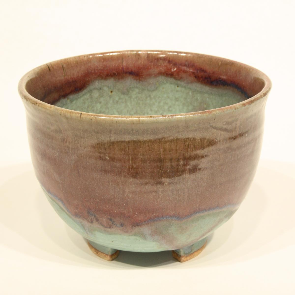 Elegant ceramic bowl with green and brown colors merging together.