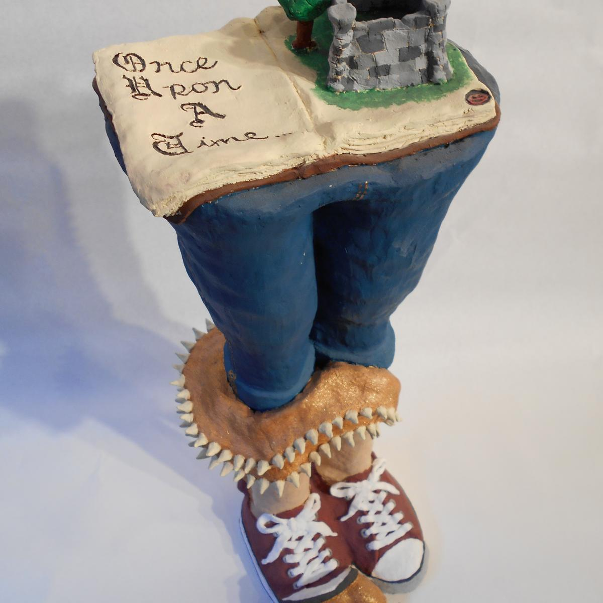 "Ceramic sculpture of two legs on top of which is an open fairy tale book with a castle coming out of a page and the words ""Once Upon A Time"" on the opposite page. Out of one leg is straw like the scarecrow from Wizard of Oz and three talons come out of a red tennis shoe."