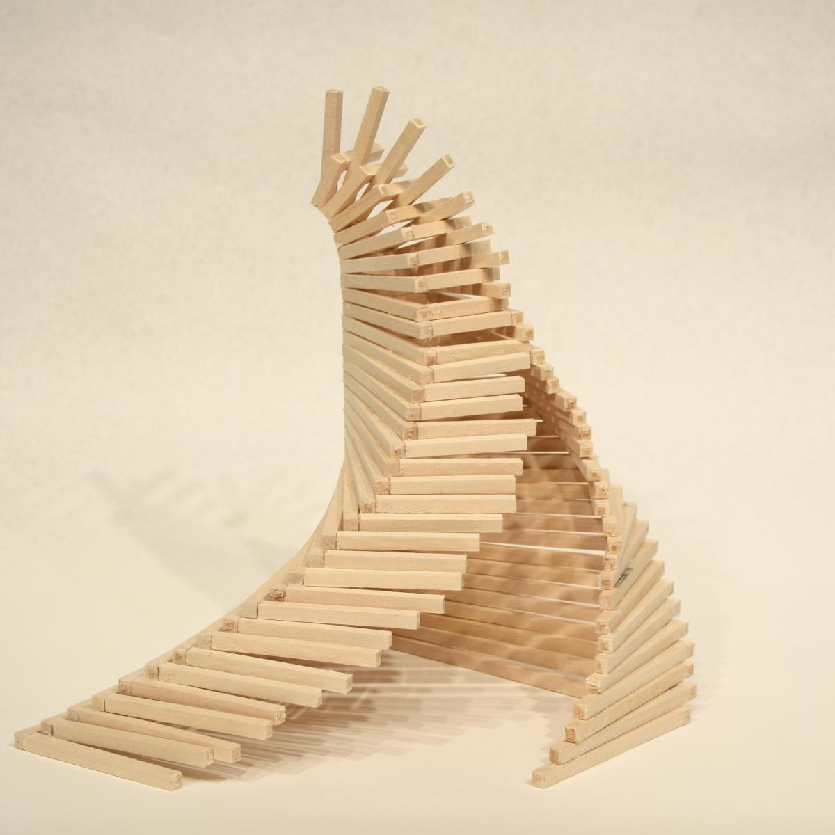 Wooden sticks piled together to form a curving tower with a split opening.