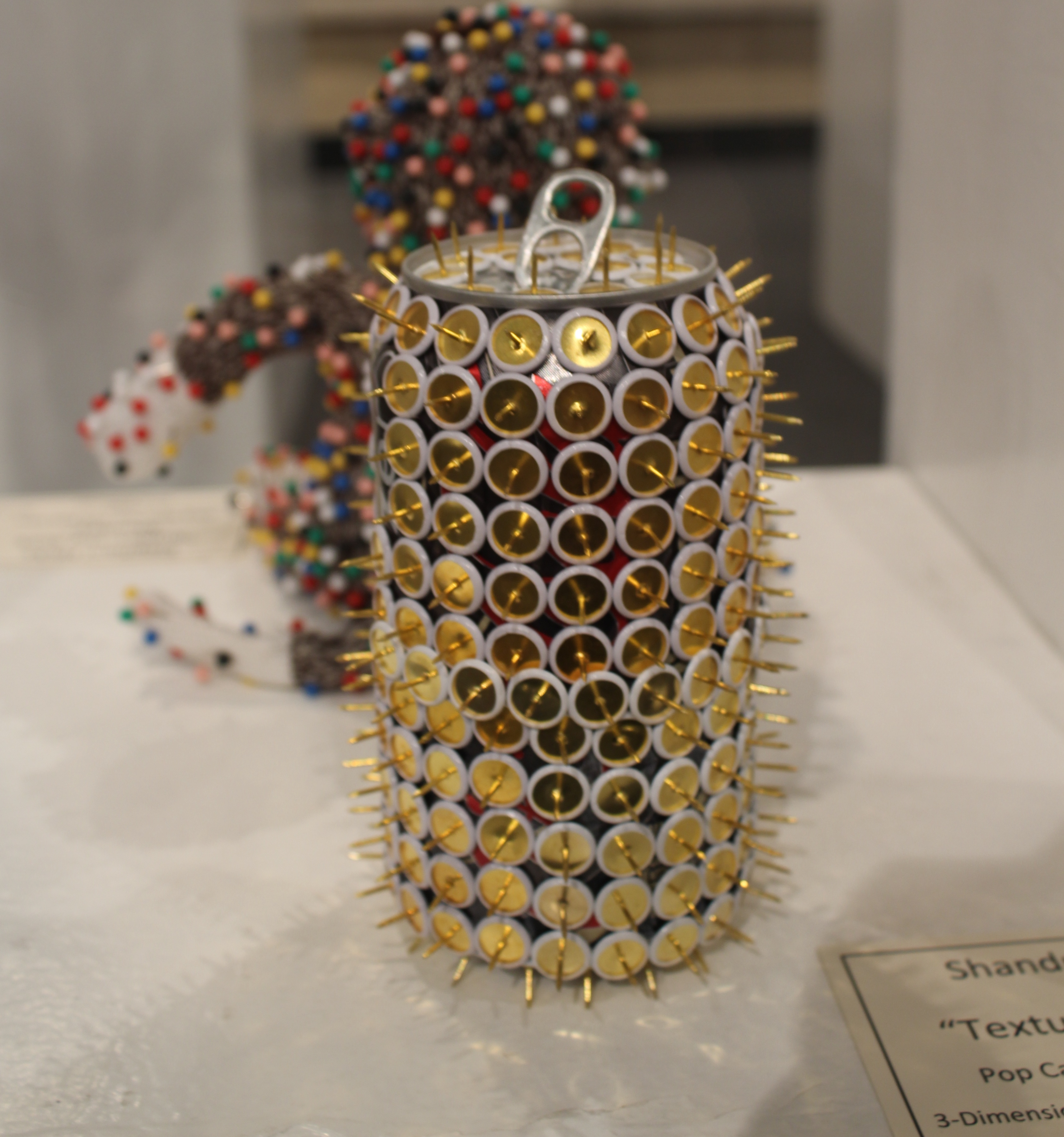 """Texture"" by Shandra Dicks - pop can covered with golden thumb tacks sharp end pointed outward."